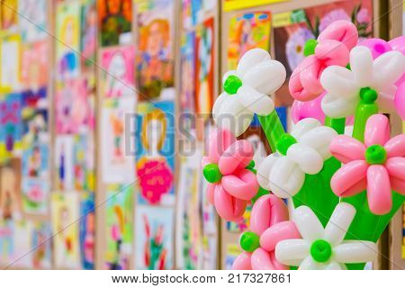 Competition of children's drawings. Exhibition of children's art. Colorful balloons in the foreground. Defocused background.