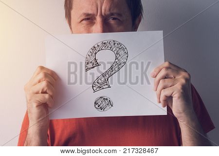 Question mark looking for answers. Man holding paper with scribbled interrogation point query or eroteme punctuation