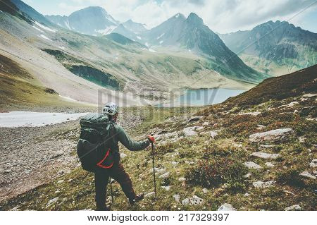 Adventurer man hiking in mountains with backpack Travel Lifestyle hiking adventure concept summer vacations outdoor exploring wild nature