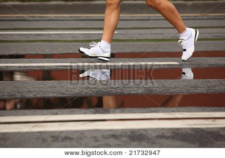 Running man's naked legs in jogging shoes on asphalt with puddles, focus on the front foot poster