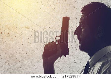 Man with a gun. Police officer criminal investigation detective or secret service agent. Grunge edit.