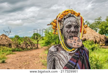 OMO VALLEY, ETHIOPIA - MAY 7, 2015 : Woman from the african tribe Mursi with a big lip plate in her village.