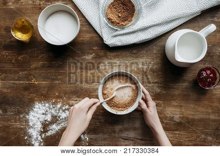 cropped shot of woman preparing ingredients for baking pancakes with sieve of flour in hand