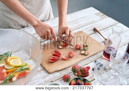 Woman slicing fresh strawberries to add to the fruit punch cocktail mocktail for fourth of july party