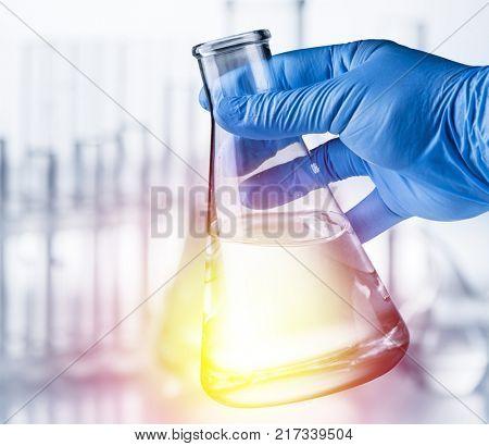 Laboratory beaker in analyst's hand in plastic glove.