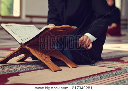 An open Holy quran with wood stand with praying people in background.