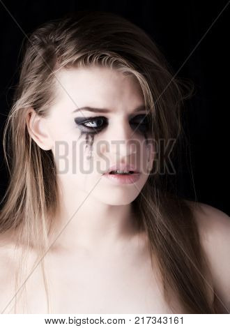 young beautiful woman crying on dark background