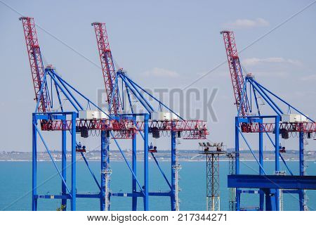 Deserted port terminal in a harbour for loading and offloading cargo ships and freight with rows of large industrial cranes to lift goods off the decks and from the holds.