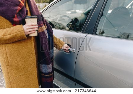 partial view of woman with coffee to go in hand holding car door handle