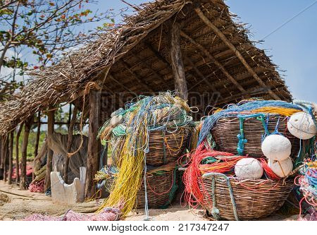 Color fishing net floats nylon rope used in fishing industry on the beach in big wicker baskets in small fishing hut.