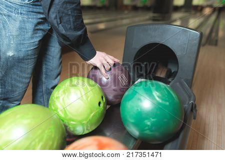 The ball in a bowling alley, with beauty color. The hands of the man chosen ball for bowling. Color balls for bowling.