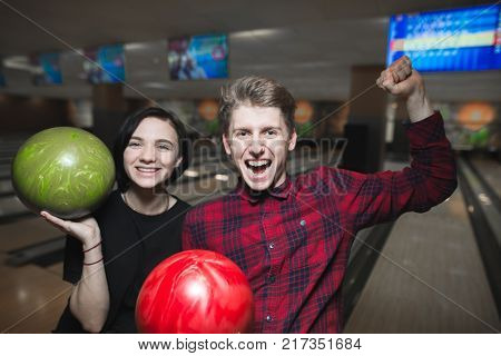 Bowling game. Happy young people with bowling balls lifted their hands upward with joy. Bowling players have won.