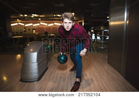 He is a winner. Handsome young men throwing a bowling ball while three people cheering. Young man playing bowling with a blue ball for bowling. A man throws a bullet on a stick.