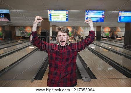Happy young man made a bowling strike. The student raised his hands from joy while playing bowling. Bowling victory