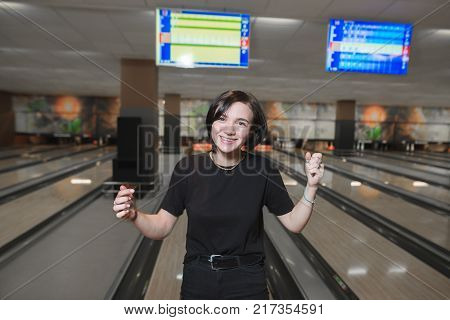 Happy girl won the bowling. A young girl is glad to do a bowling strike. Active leisure for bowling