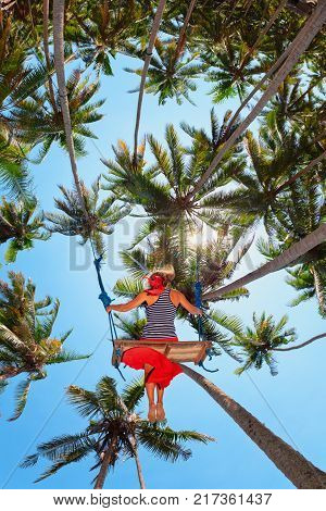 Young happy girl have fun swinging high in mid air. Flying up upside down on swing among palms on sea beach. Adventure in tropical island. Travel lifestyle activity on summer family vacation with kid