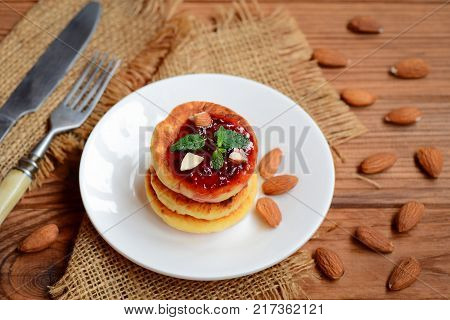 Fried cottage cheese pancakes with berry jam, almonds nuts and mint on a served plate. Delicious cottage cheese almond flour pancakes