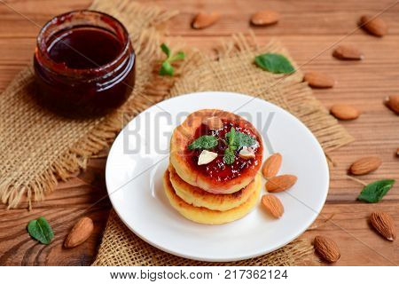 Fried cottage cheese fritters with berry jam, almonds nuts and mint on a served plate. Yummy cottage cheese almond flour fritters. Healthy cottage cheese breakfast idea