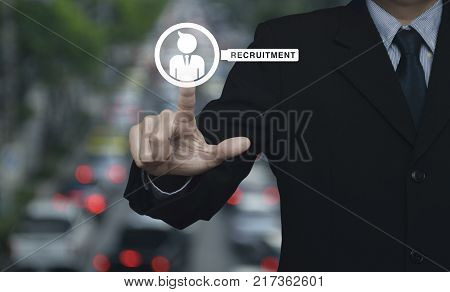 Hand pressing businessman with magnifying glass icon over blur of rush hour with cars and road Business recruitment concept