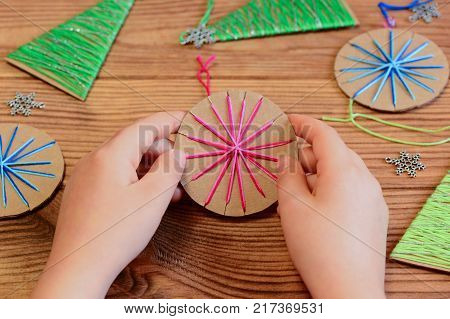 Child is holding a Christmas ball decor in his hands. Child is showing a Christmas ball decor. Simple recycled crafts and activities for kids. Christmas decor set on a wooden table