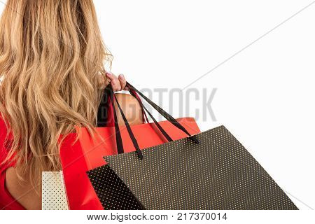 Back view of woman carrying shopping bags on shoulder isolated on white background with text area.