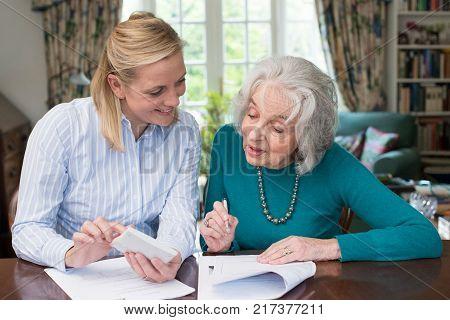 Friendly Woman Helping Senior Neighbor With Paperwork