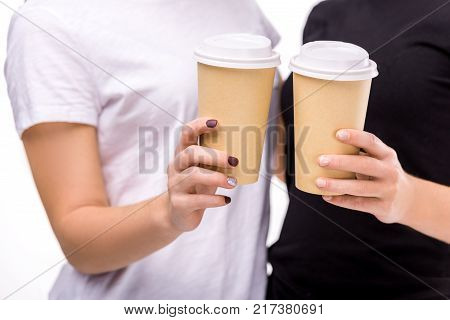 partial view of women holding coffee to go in hands isolated on white