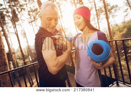 An elderly man and a fitness instructor are talking in a nursing home. They were engaged in medical gymnastics. They are standing outdoors and they are in a good mood.