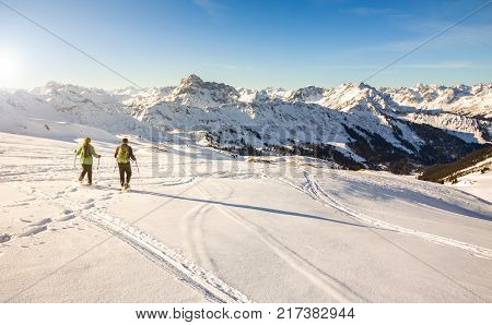 Couple hiking with snowshoes at sunset in winter mountain landscape. Alps in Germany, Bavaria, Allgau.