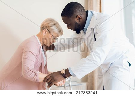 The doctor helps to get out of bed an elderly woman in a nursing home. They have just finished a medical examination. He holds her hands. A woman holding on to a walker for adults.