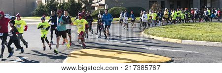 Wet Islip NY USA - 24 November 2017: The annual Run Your Turkey Off 4K road race with runners starting in a parking lot and entering the road to run through the neighborhood.