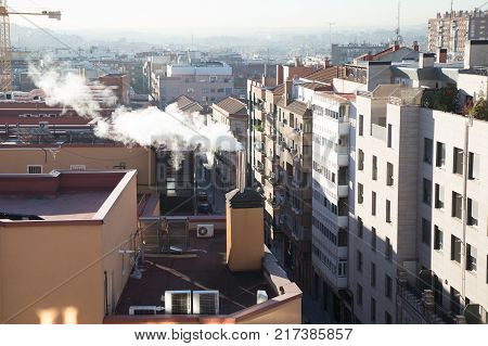 smoke raising from chimney of heating fossil fuel in rooftop of building in Madrid city Spain Europe