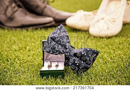 Wedding rings bow tie and women's and men's shoes on the green grass. Symbol of love. Yellow photo filter.