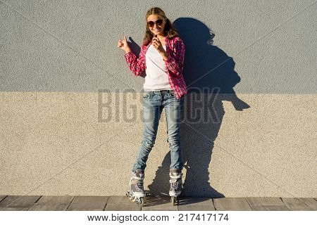 Portrait of young cool girl, shod in rollerblades holding chocolate bar and showing thumbs up. Thumb up energy and joy