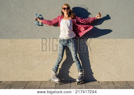 Outdoor portrait of a happy teenage girl with a chocolate bar and a bottle of fresh water. The girl is shod in the roller skates