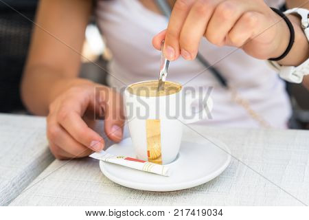 Woman mixing coffee with a spoon, closeup, street cafe, sugar packets