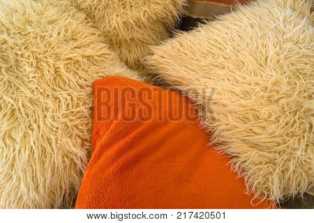 Beige and orange artificial wool cushions on the couch