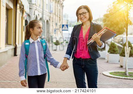 Outdoor portrait of a schoolgirl and her teacher.