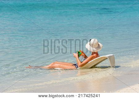 Woman Lying On A Deckchair In The Ocean Maldives Indian Ocean. Copy Space For Text