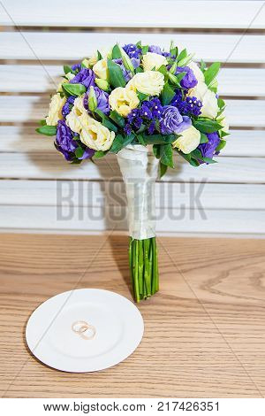 Beautiful bouquet of wedding and engagement rings on the table