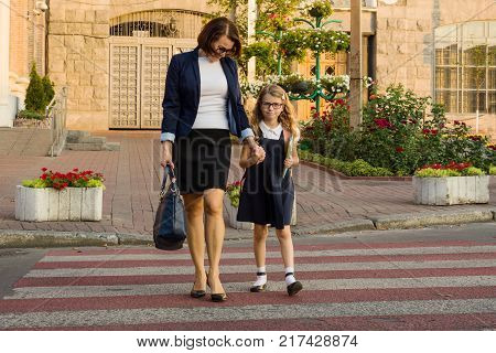 Woman and  child - a young schoolgirl holding hands, on zebra crossing. Education for childcare and love.