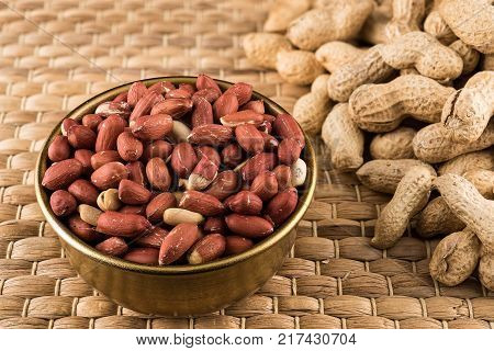 Bronze bowl of peeled peanuts and peanuts in nutshell on natural matting