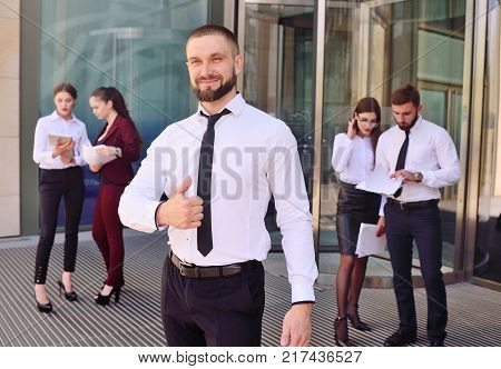 young man in office business suit smiling and showing thumb - sign class. Success in business