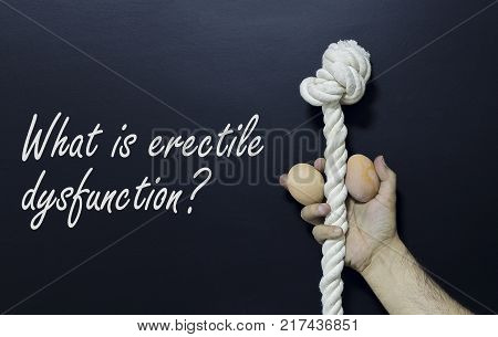 Written text: What is erectile dysfunction. Man holding rope and two eggs as symbol of male penis on black surface