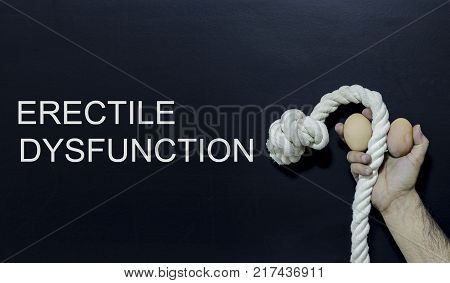 Written text: erectile dysfunction Man holding rope and two eggs as symbol of male penis on black surface