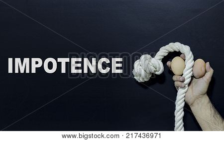 Written text: Impotence. Man holding rope and two eggs as symbol of male penis on black surface