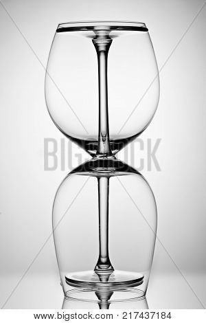 Two empty wineglass for red wine on diffusion lit background in abstract  composition with reflection, advertizing shot for restaurant, winemaking B W