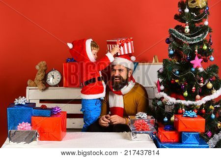 Christmas Family Opens Presents On Red Background.