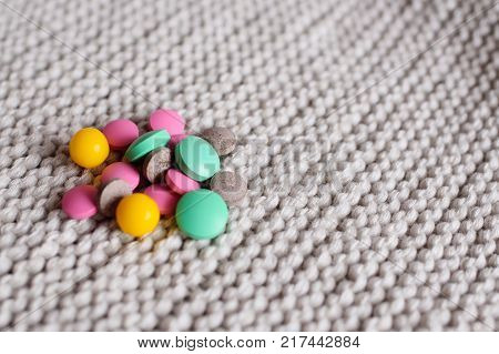 many multi-colored tablets and vitamin close-up on a knitted background. copy space