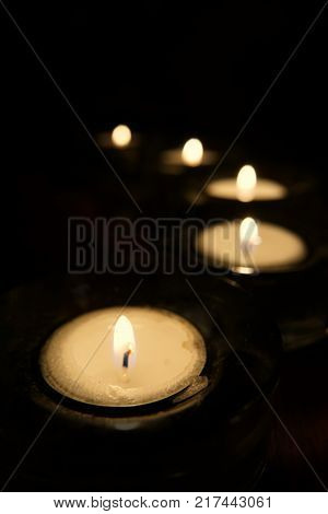Lit Candles in a curving pattern with fall off focus and shadow background